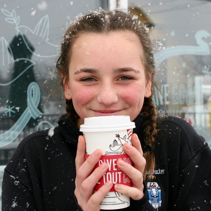 Young teenage girl enjoying a starbucks holiday drink outside in the snow