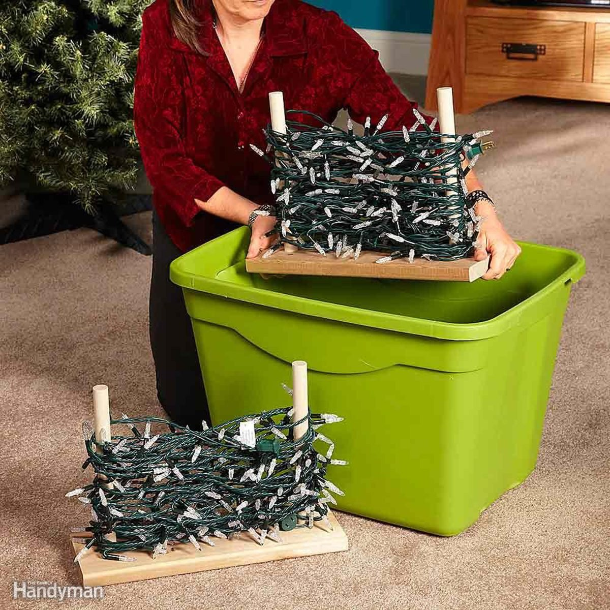 Storing Christmas lights wrapped around wooden pegs and being put into a lime green plastic tub