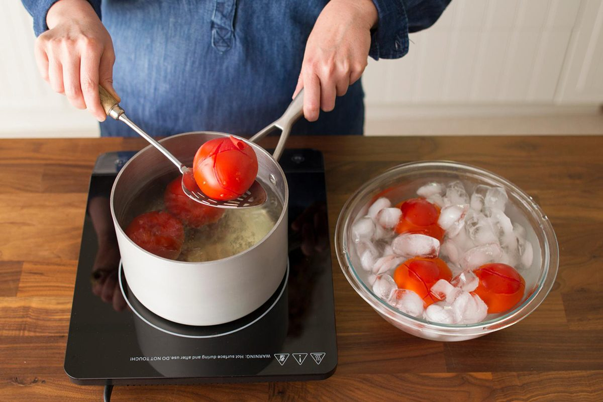 woman placing tomato in ice bath from boiling pot
