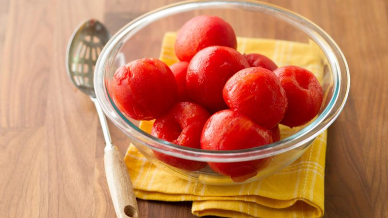 peeled tomatoes in glass bowl