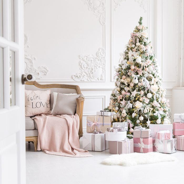 Luxury living room interior with sofa decorated chic Christmas tree, gifts, plaid and pillows