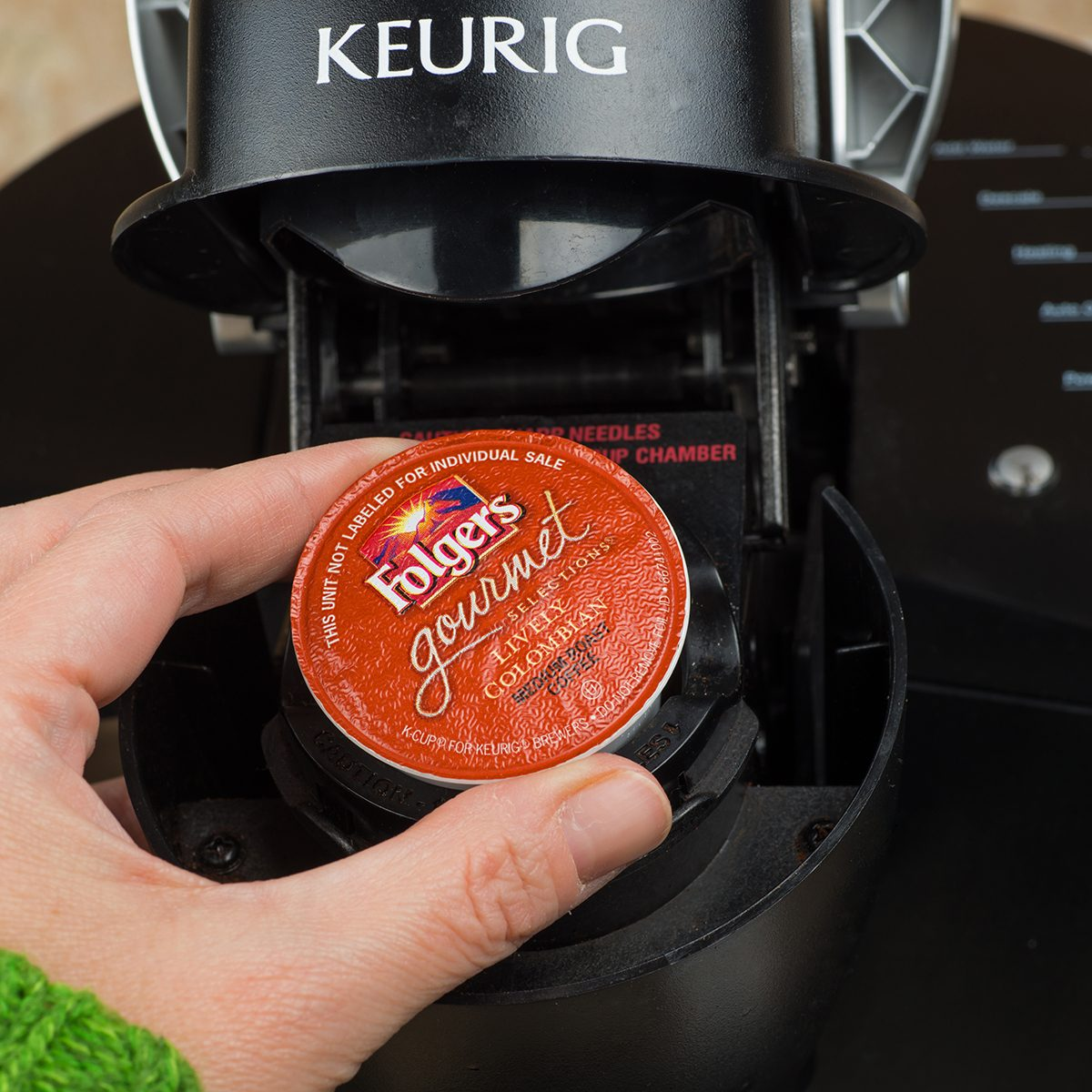 Close-up of woman inserting single-serve K-cup Foldger's coffee into a Keurig coffee maker.