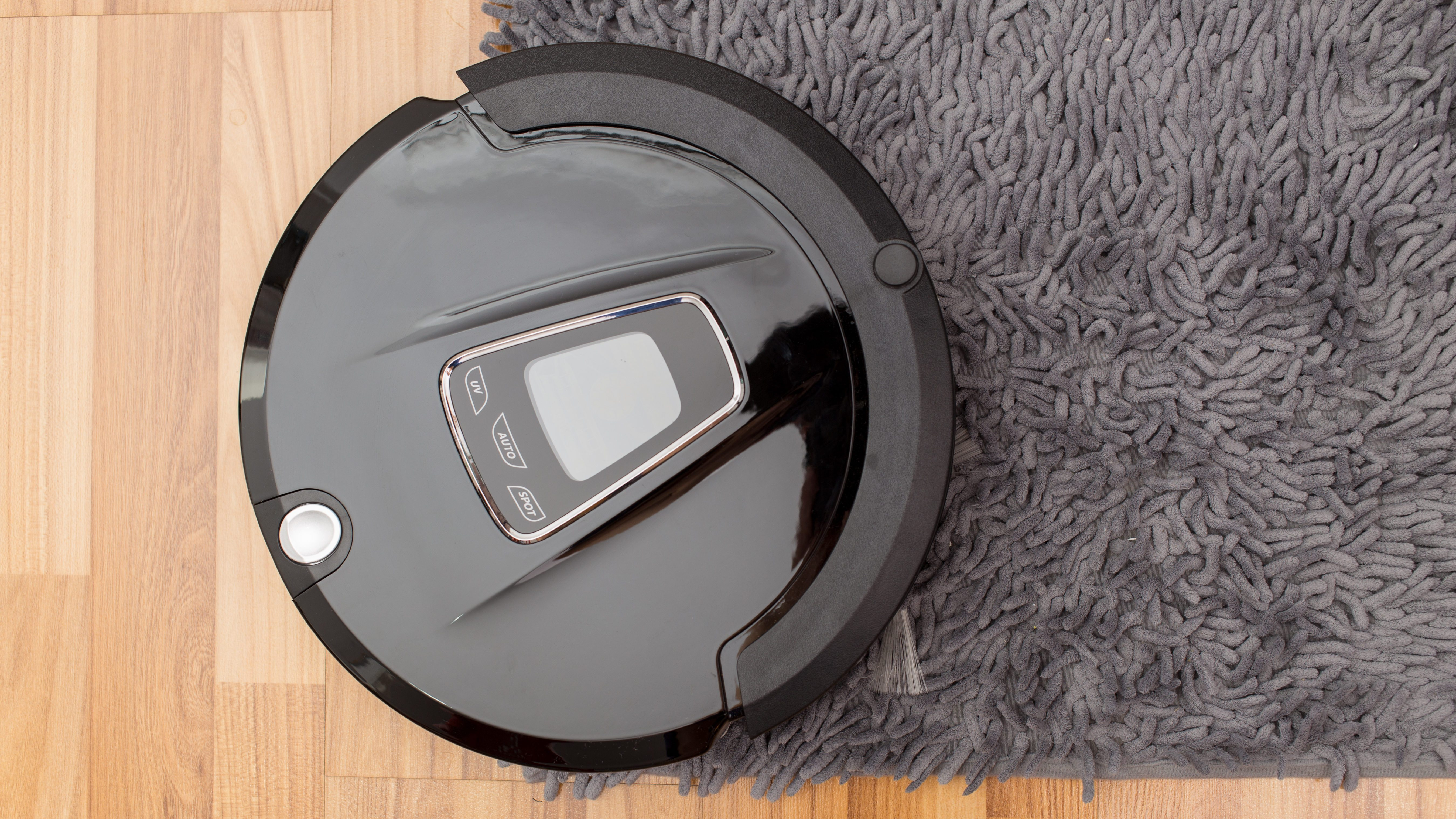 Robot vacuum cleaner on laminate wood floor, Smart robotic automate wireless cleaning technology machine in living room.