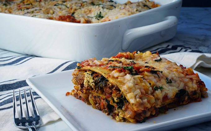 Photo of a pan of vegan lasagna with a slice on lasagna on a plate