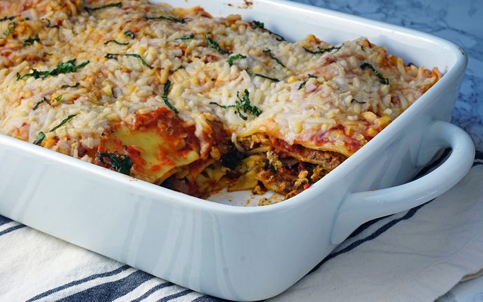 Photo of a baked vegan lasagna with a slice removed
