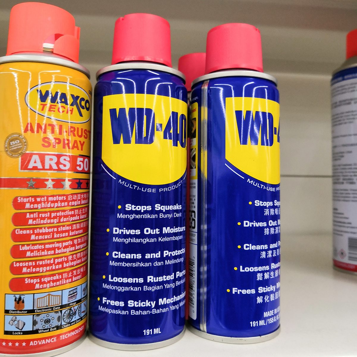 A bottles WD 40 lubes brand display at supermarket shelf.