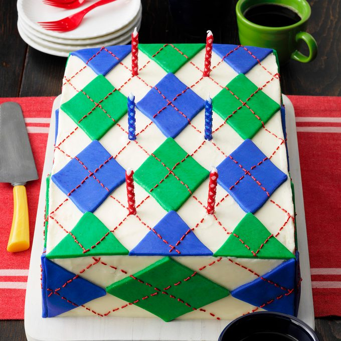 Wacky Argyle Cake; 3/4 camera angle; dark wood surface; large cake; candles; birthday candles; green mug; blue mug; coffee; coffee mugs; coffee mug; red plastic forks; plastic forks; frosting; fondant; red runner; red table cloth; white plate stack; plate stack; cake knife; cake server; white cutting board; rustic wood surface