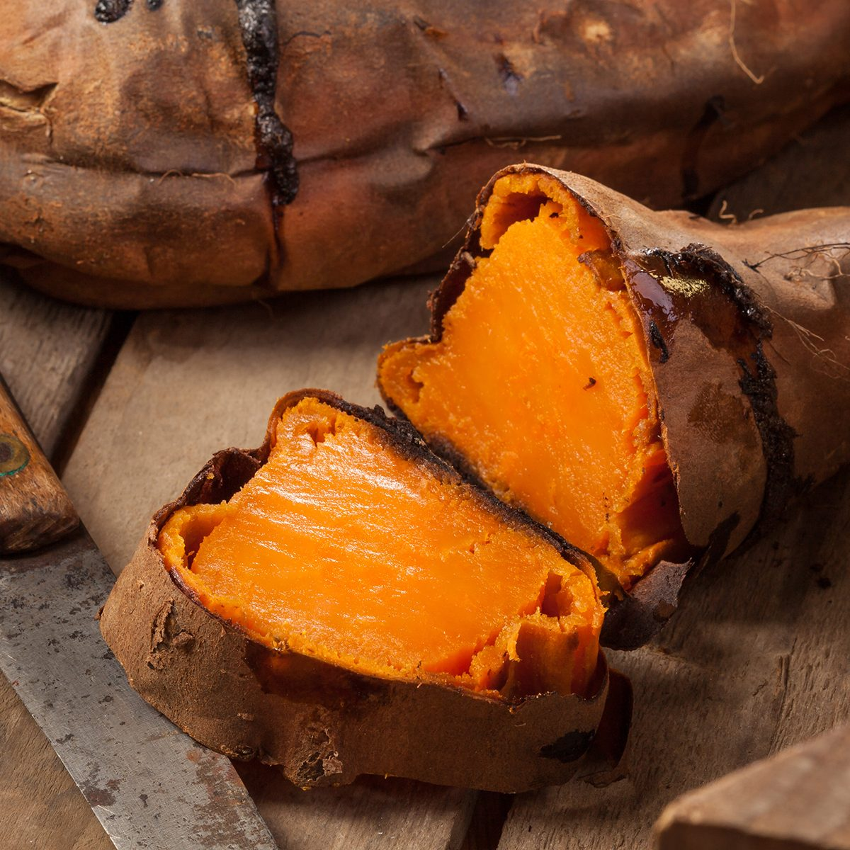 Oven baked sweet potatoes on vintage wood.