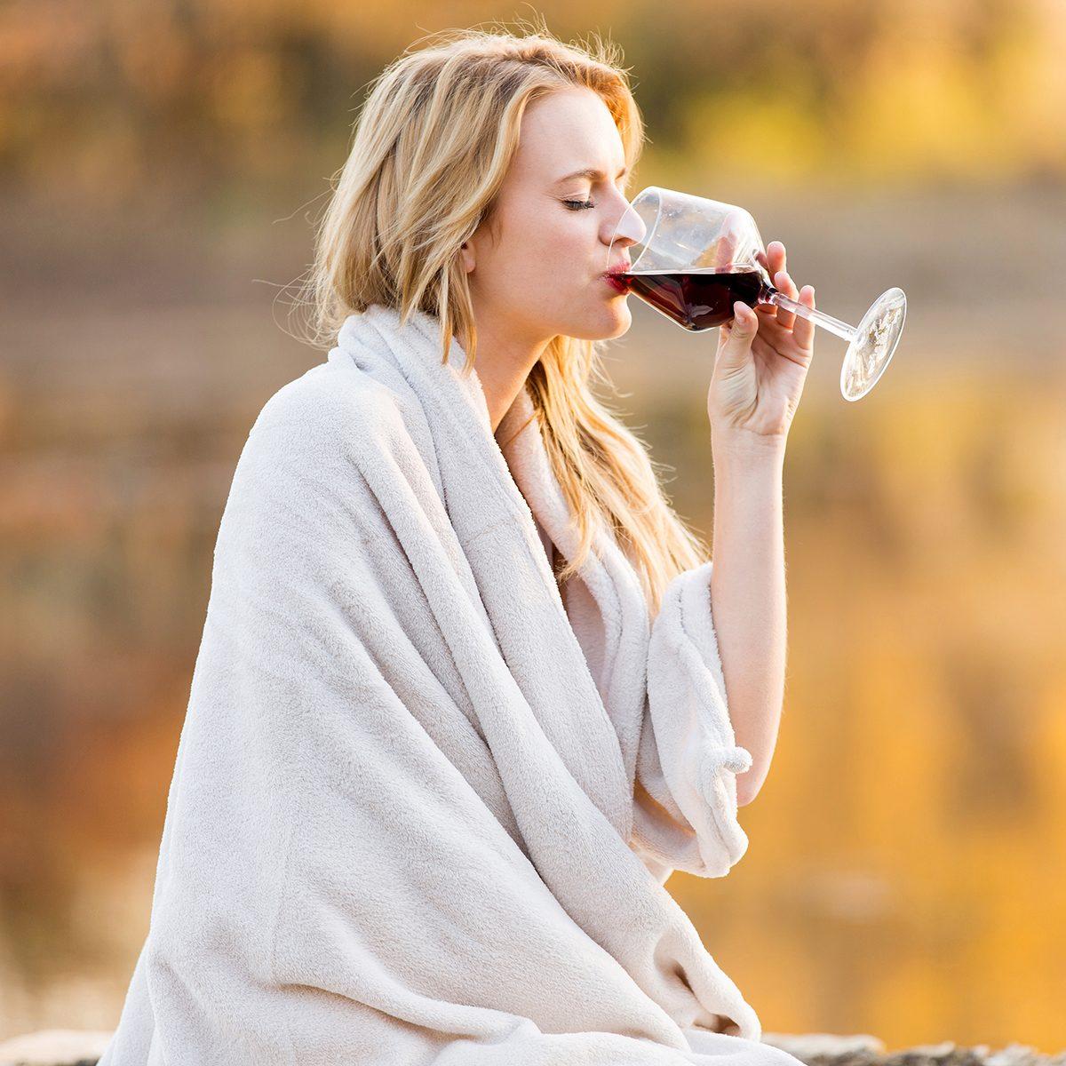 beautiful blond woman drinking red wine at sunset