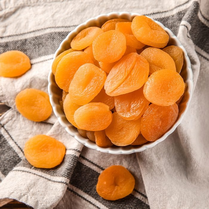 Bowl with dried apricots on table