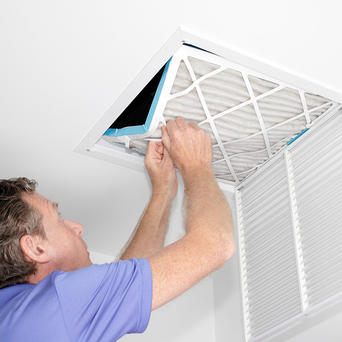Mature man taking out a dirty air filter from a home ceiling air return vent.