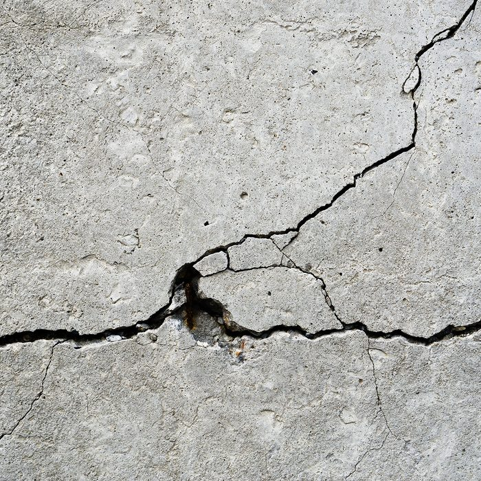 Horizontal rusty crack in concrete textured background
