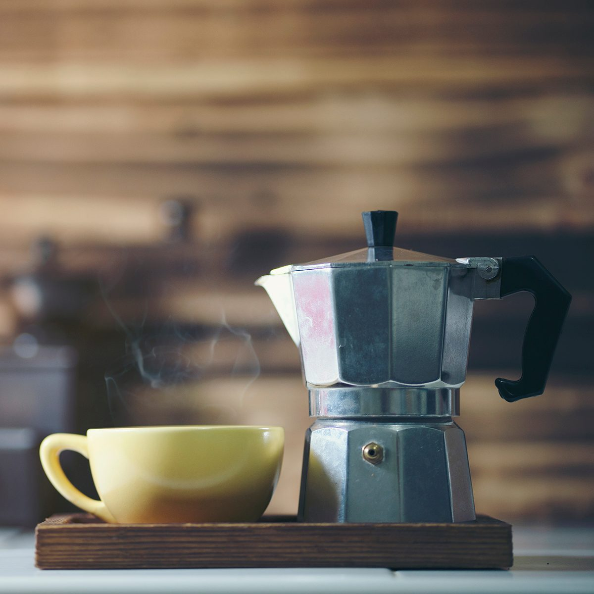 cup of coffee with metal coffee percolator on wooden background