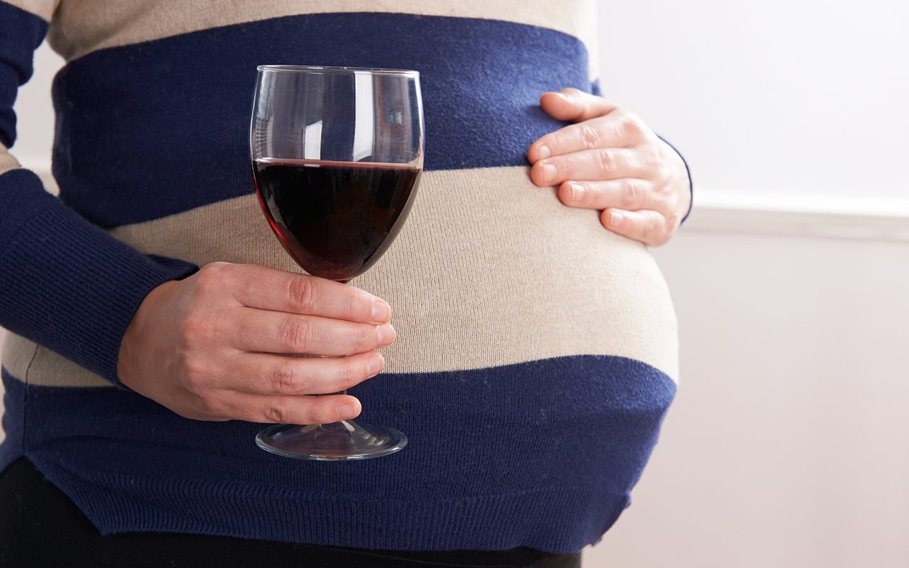Detail Of Pregnant Woman Drinking Glass Of Red Wine