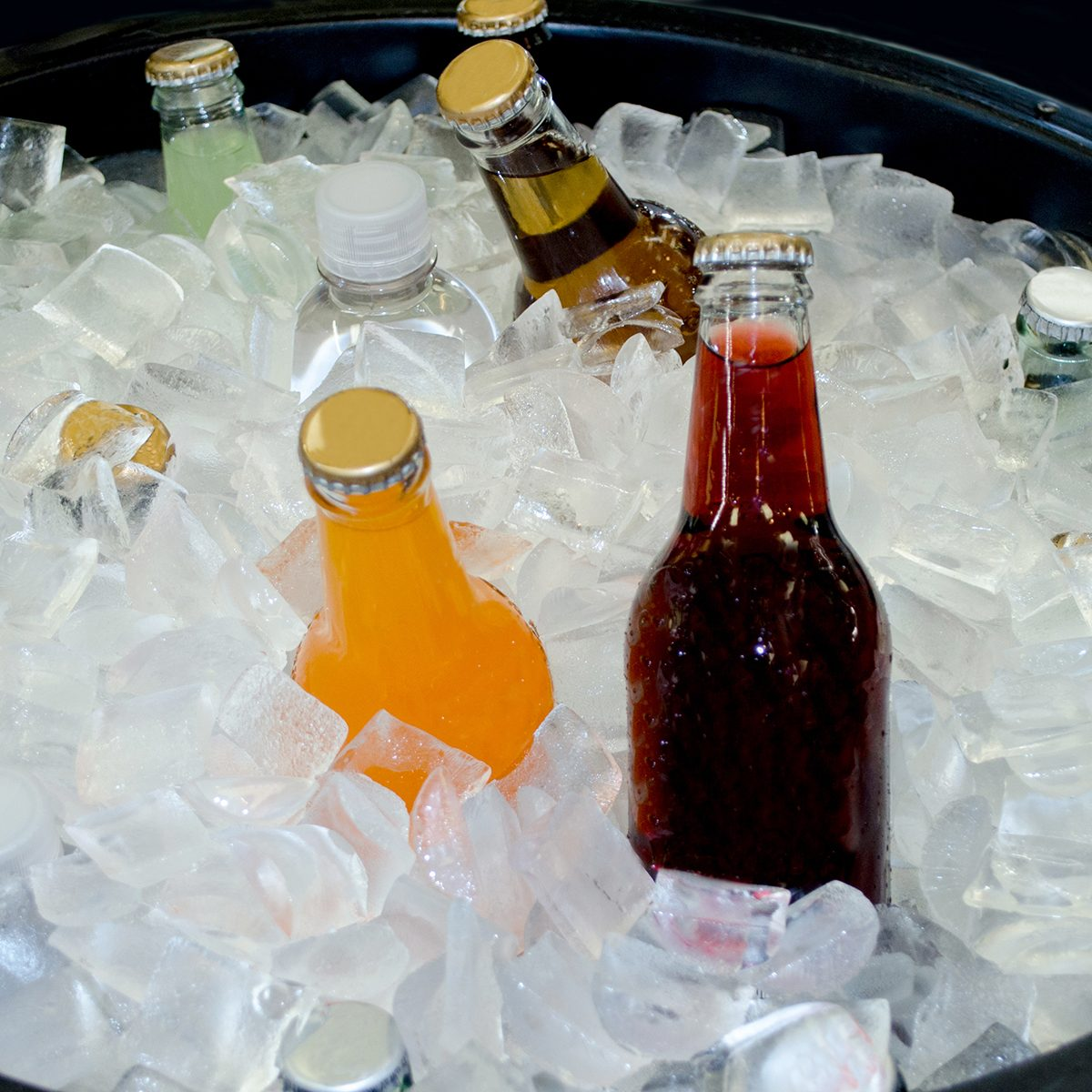 bottles of various kinds of soda chill in a large in of crushed ice