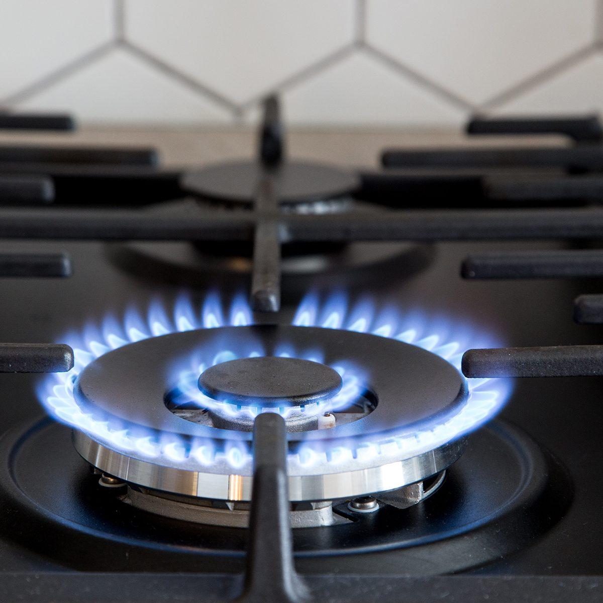 Gas burner on black modern kitchen stove.