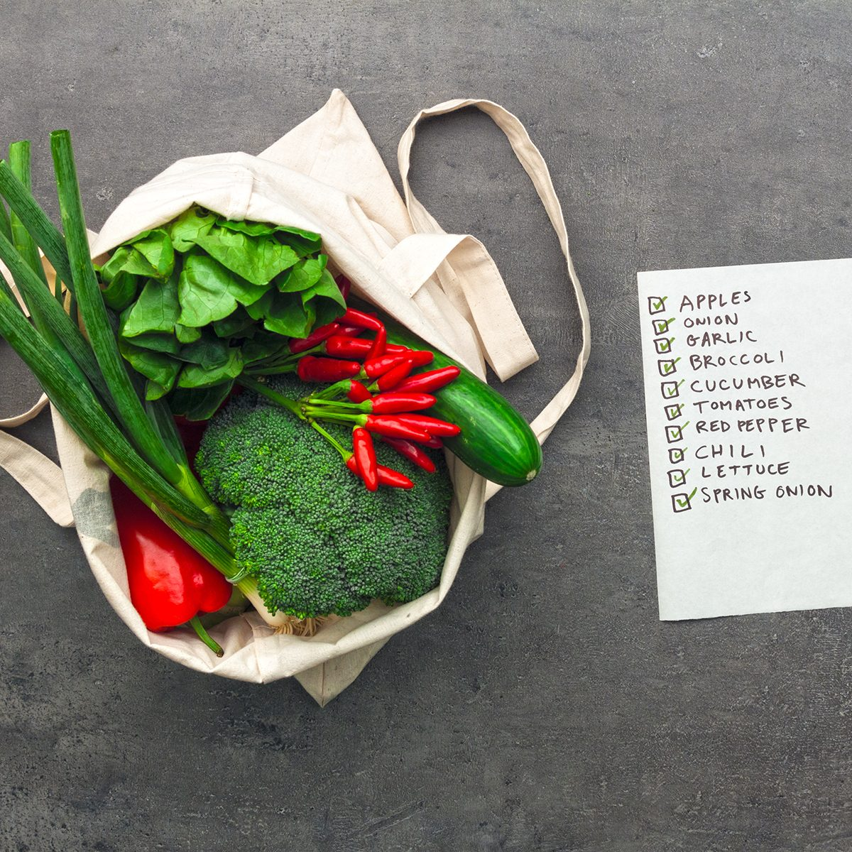 Shopping bag full of vegetables and fruits with checked shopping list.