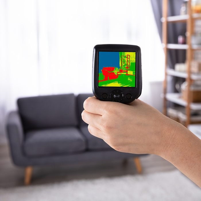 Woman's Hand Using Infrared Thermal Camera To Check Temperature In Living Room