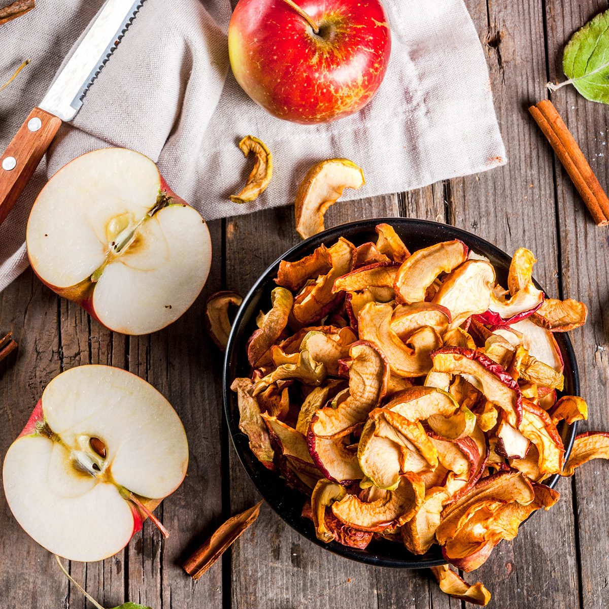 Homemade sun-dried organic apple slices, crispy apple chips, on an old rustic wooden table with fresh apple and cinnamon. Copy space top view