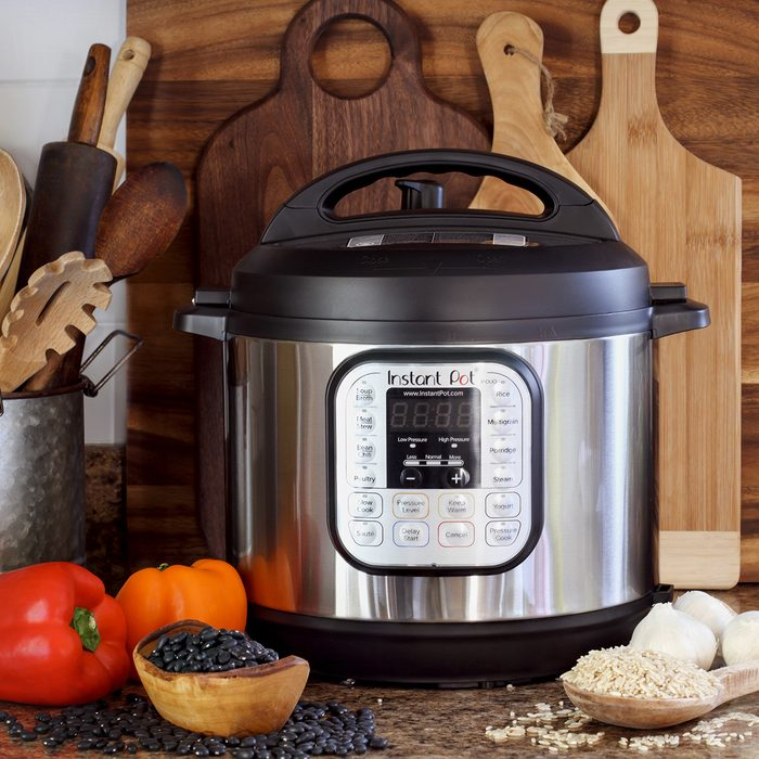 Instant Pot pressure cooker on kitchen counter with beans and rice.