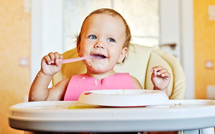 laughing eating girl with baby barley cereal