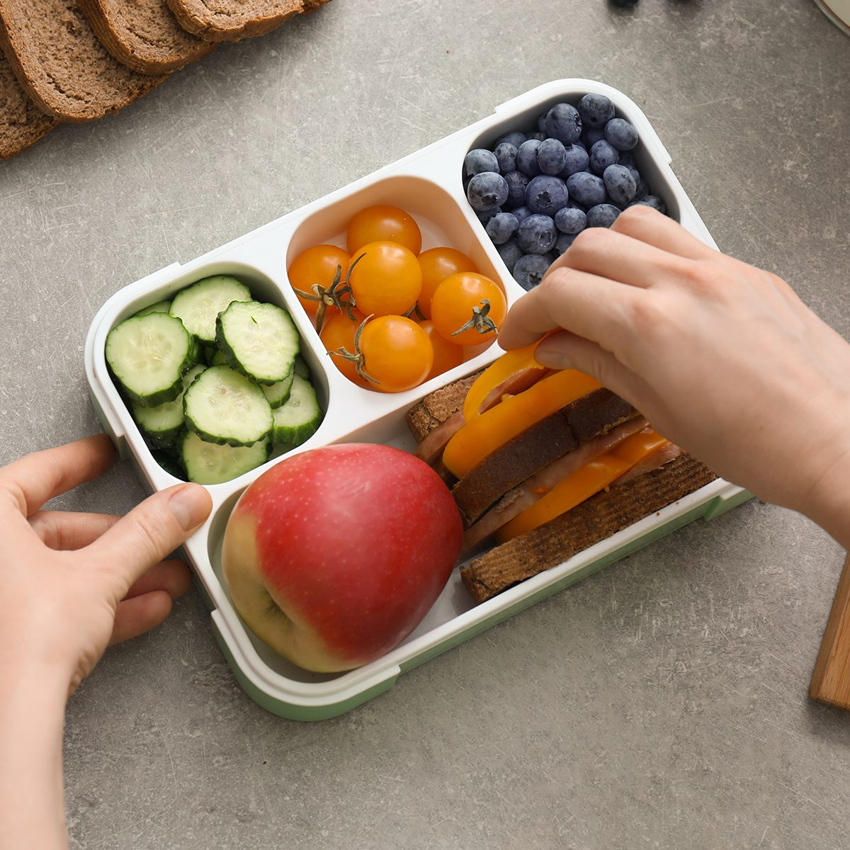 Mother putting food for schoolchild in lunch box on table