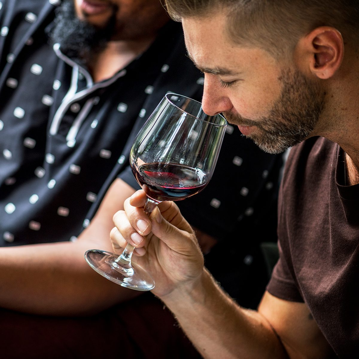 Man tasting red wine with friends