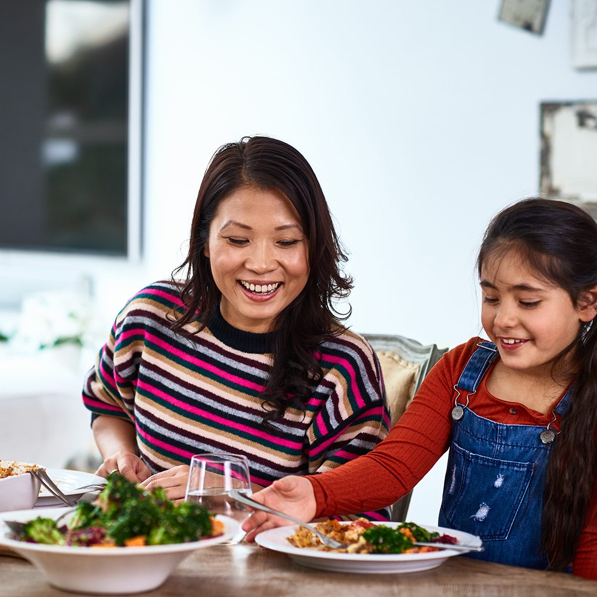 Cheerful family dinner in dining room, mid adult woman smiling at daughter eating food, good choice, positive parenting