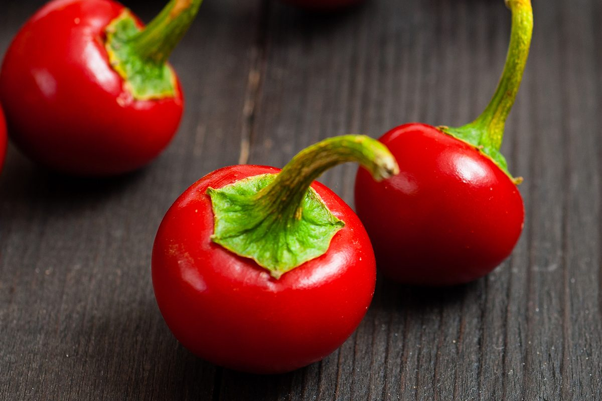 cherry peppers on old black wooden table background
