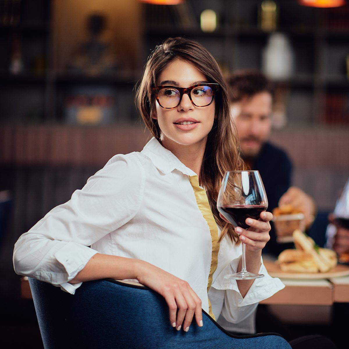 Portrait of gorgeous brunette looking away and holding glass with red wine while sitting at restaurant.