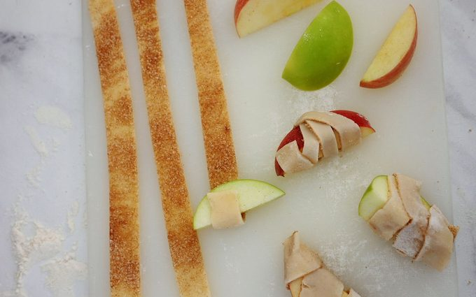 Wrapping apple slices in the sugary dough