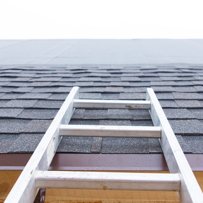 Ladder leading to an unfinished roof on a new house showing the installation of new roofing tiles and the waterproof membrane