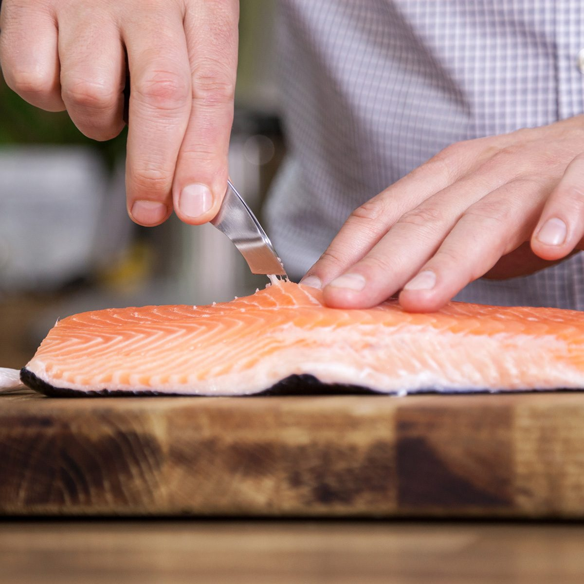 Close up of man removing fish bone out from salmon and preparing food in the kitchen.
