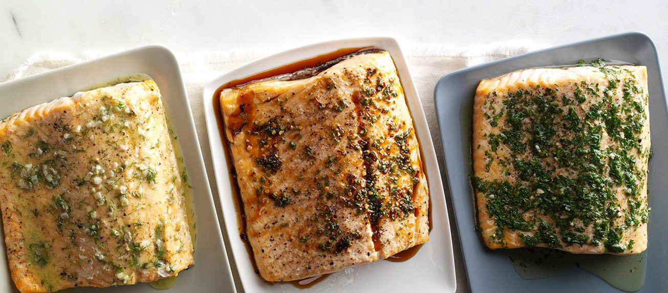 Three cooked salmon fillets with different types of sauce