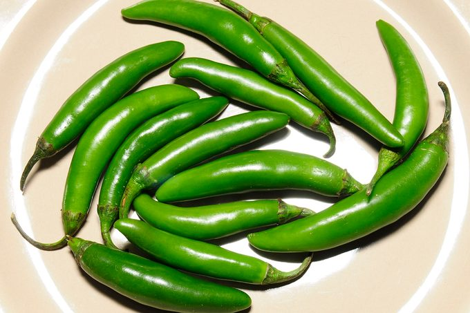 Chiles serranos on a plate and white background