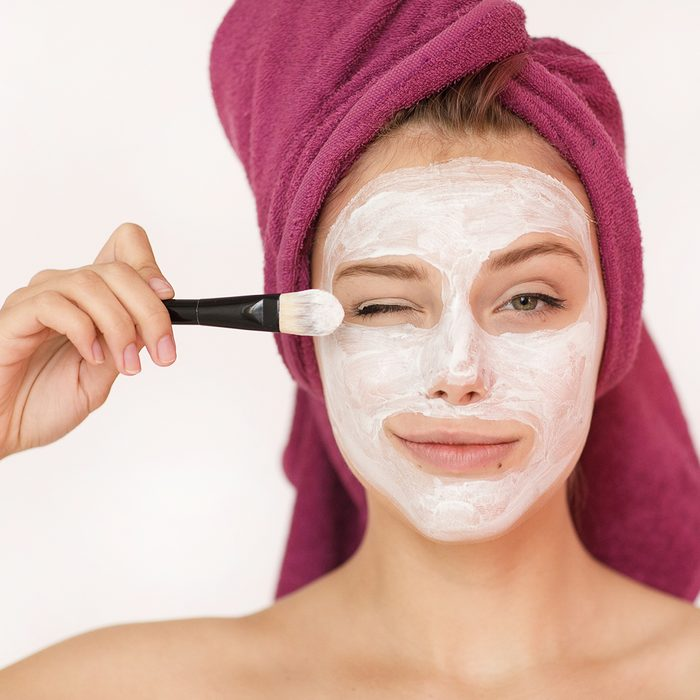 Happy and cheerful beautiful woman with a towel on her head and a cosmetic mask of white clay on her face looking into the camera applying a brush solution on her cheek isolated on a white background