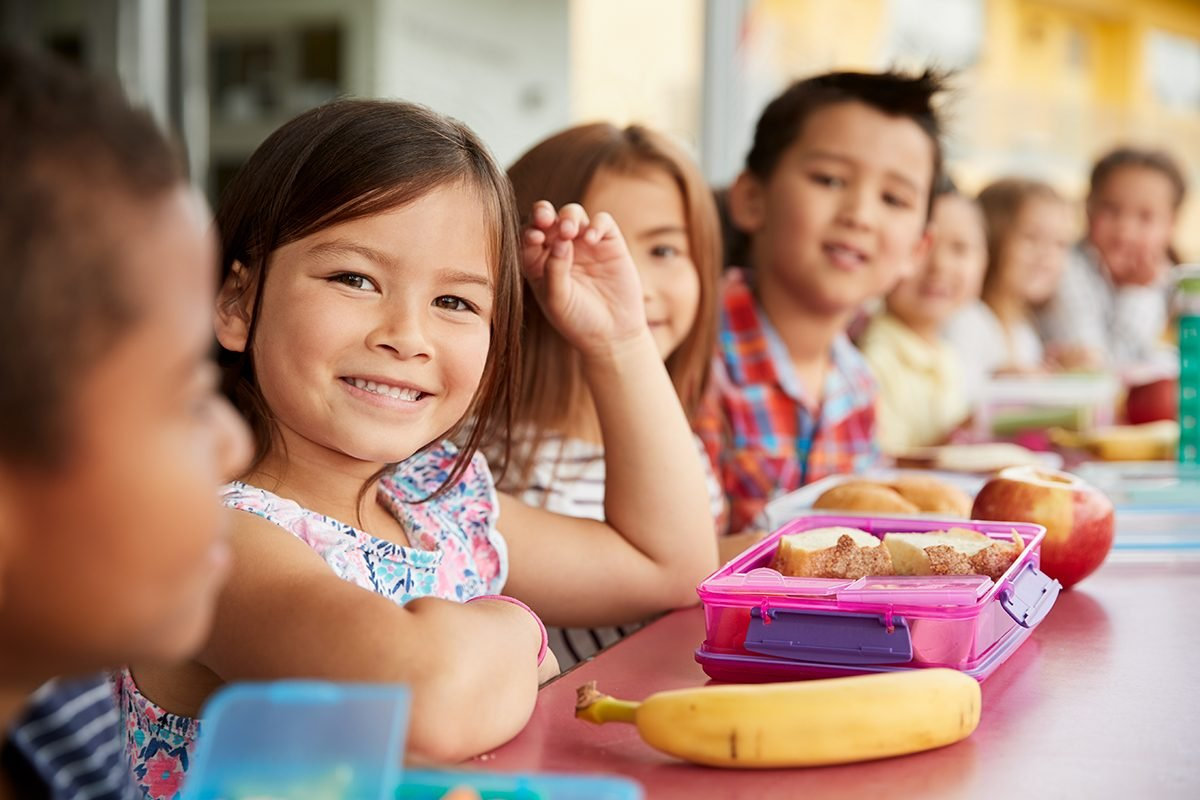Elementary school kids sitting a table with packed lunches; Shutterstock ID 1177724563; Job (TFH, TOH, RD, BNB, CWM, CM): Taste of Home