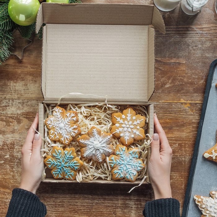 cropped shot of woman holding box with homemade christmas cookies on wooden tabletop with decorative christmas wreath; Shutterstock ID 1224400339; Job (TFH, TOH, RD, BNB, CWM, CM): Taste of Home
