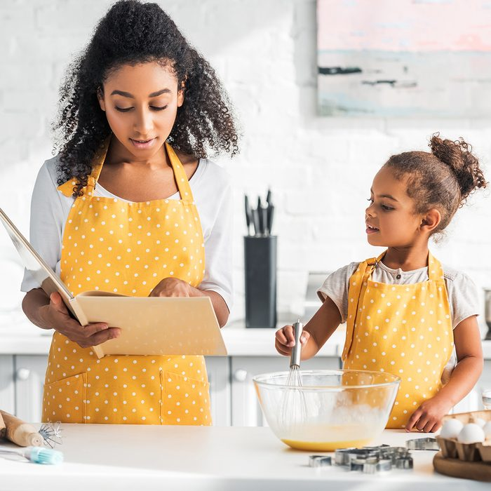 african american mother reading cookbook and daughter preparing dough in kitchen; Shutterstock ID 1229623234; Job (TFH, TOH, RD, BNB, CWM, CM): Taste of Home