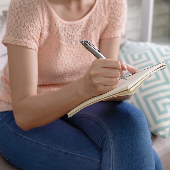 unrecognized asian woman sitting on couch in cozy living room at home. young lady holding pen and notepad writing down note in sofa. housewife creating a shopping list for groceries to market.; Shutterstock ID 1279564873; Job (TFH, TOH, RD, BNB, CWM, CM): Taste of Home