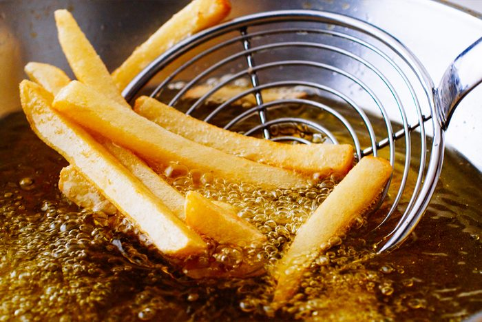 Cooking french fries. Close up of Frying french fries in the fryer in hot oil; Shutterstock ID 464044346