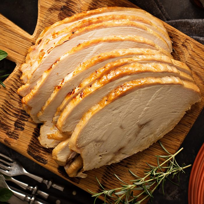 Sliced roasted tukey breast for Thanksgiving or Christmas dinner with side dishes overhead shot; Shutterstock ID 735091306
