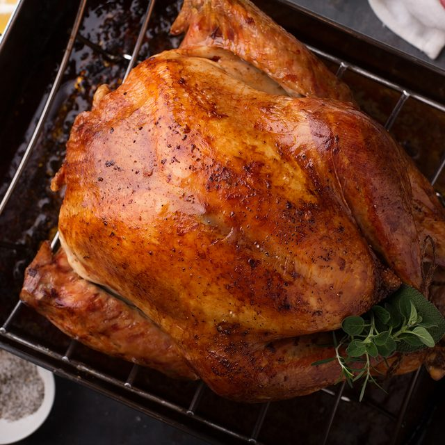 Cooked turkey for Thanksgiving or Christmas in a roasting pan ready for carving; Shutterstock ID 737627782