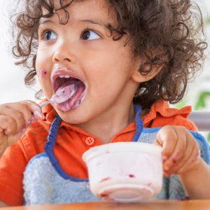 Toddler sitting in highchair and eating greek yogurt.