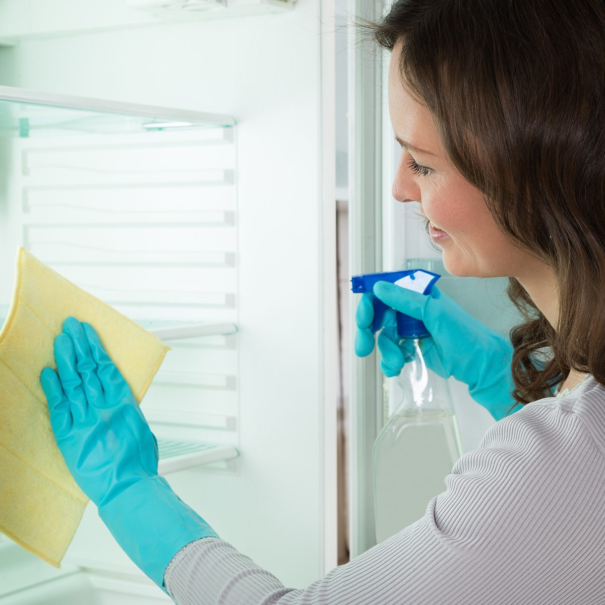 Close-up Of Young Woman Wearing Blue Glove And Cleaning Refrigerator