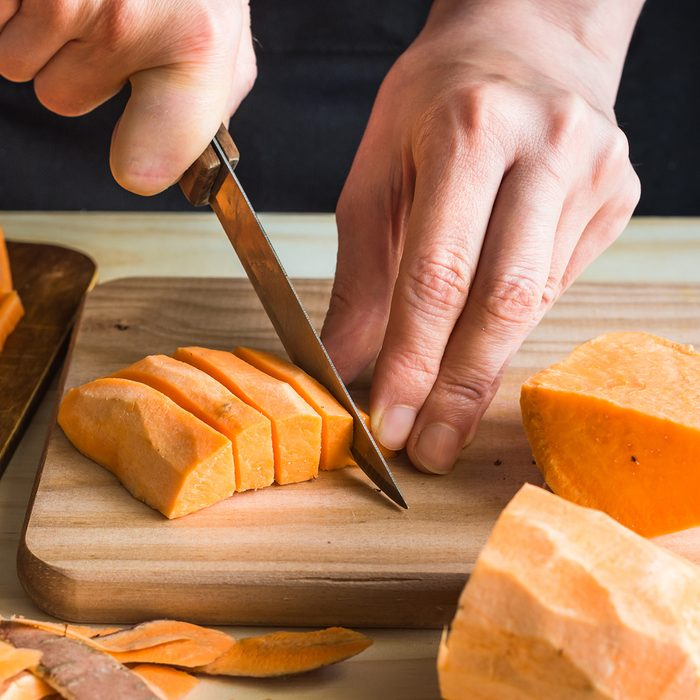 Young woman cutting with knife sweet potato into wedges, peels on wood table, sliced carrots, kitchen interior, close up
