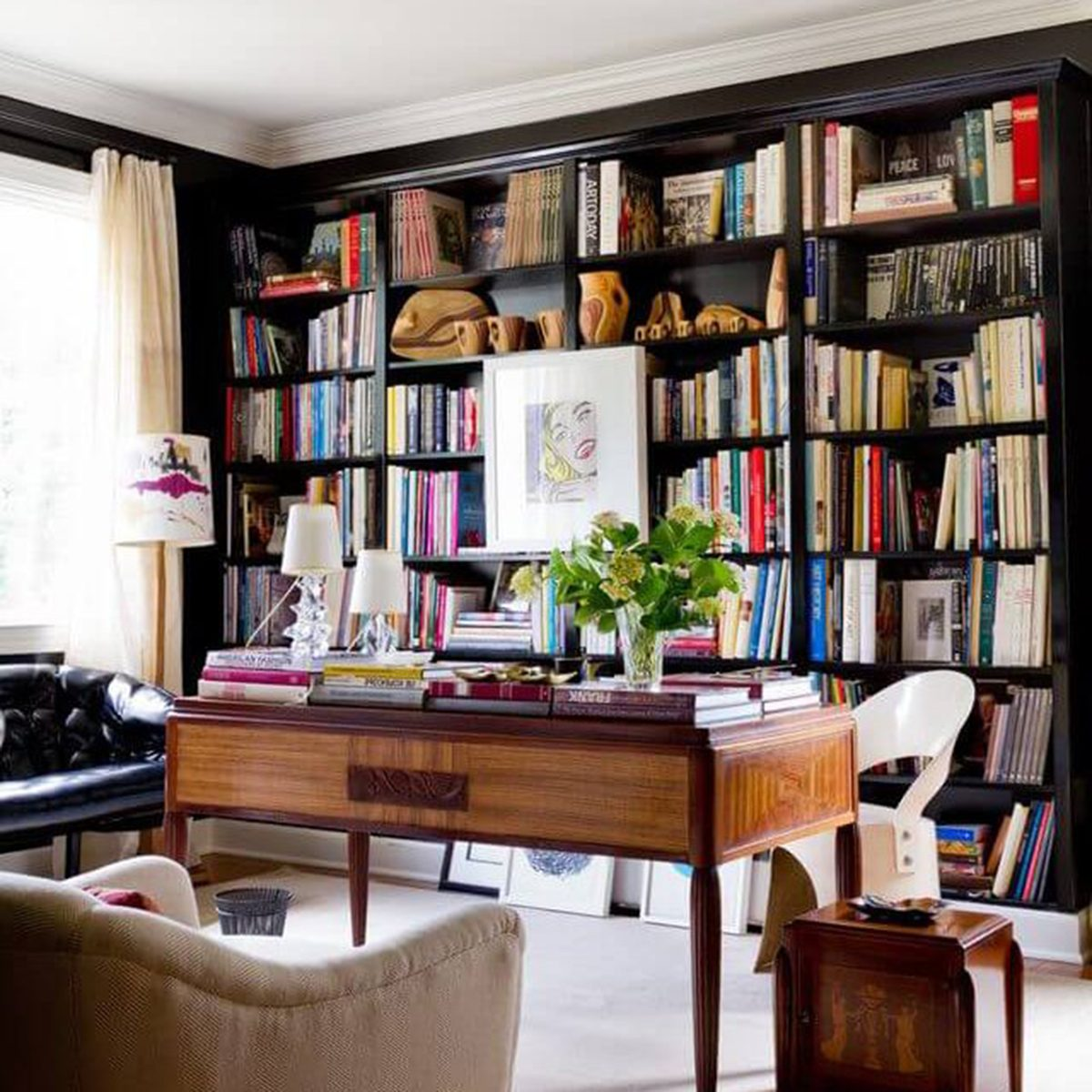 Home library filled with pop art prints, hand-carved wooden artifacts, and a slew of inspiring reads.