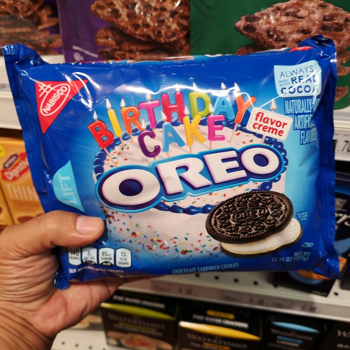 Hand hold a packet of OREO Birthday Cake flavor creme for sell in the supermarket.