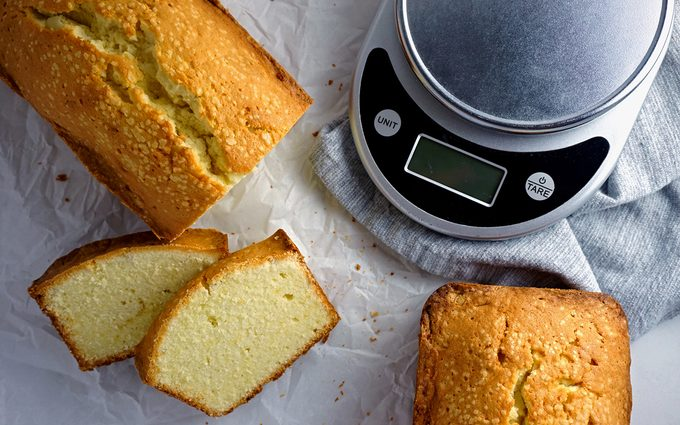 Classic pound cake loaf and slices beside a kitchen scale