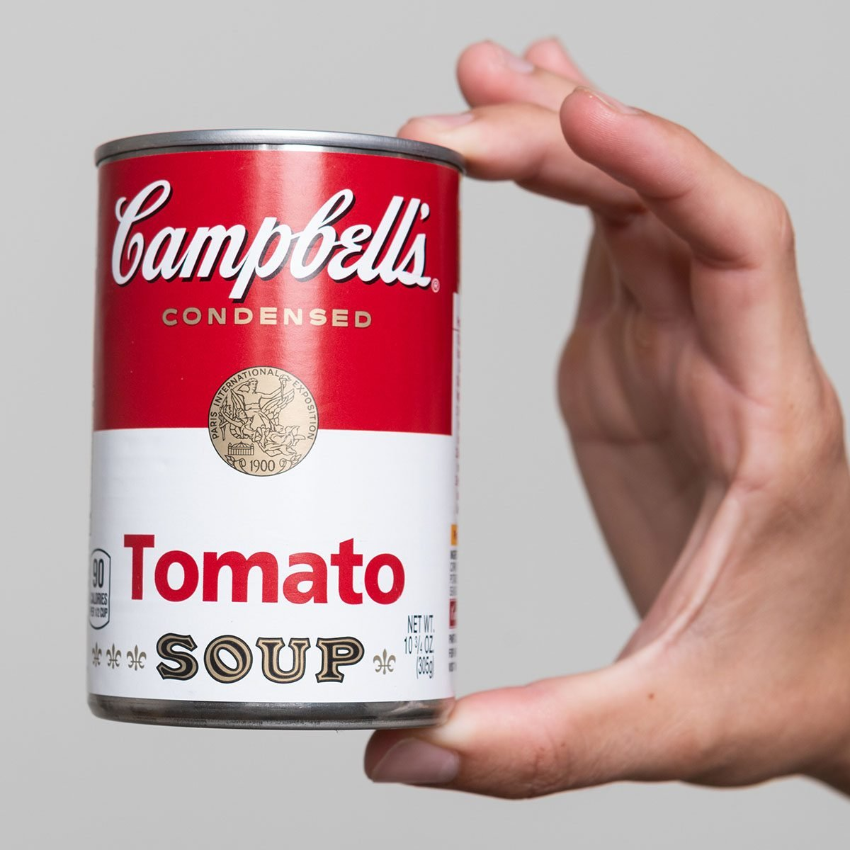 Human hand holding a tin can of Campbell's Soup tomato soup on gray background